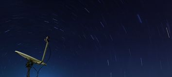 Yellow satellite over star trail Stock Photography