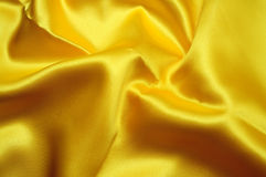 Yellow satin tissue. Backcloth of bright yellow wavy satin fabric Royalty Free Stock Images