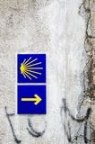 Yellow scallop shell and arrow signing the way to santiago de compostela in Galicia. Most famous pilgrimage route in Europe. Vertical caption Stock Photos