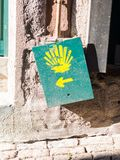 The yellow scallop shell signing the way to Santiago de Composte Stock Photos