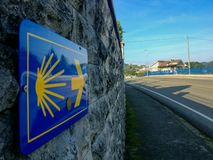 The yellow scallop shell signing the way to santiago de compostela on the Somo stock photography
