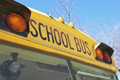 Yellow school bus. Front of traditional yellow school bus with lights and blue sky background Royalty Free Stock Photography