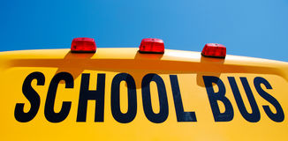 Yellow school bus. Close up of yellow school bus against bright blue sky stock image