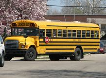 Yellow school bus. Side view of traditional yellow American school bus driving on road stock photos