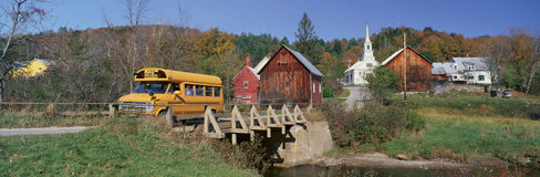 Yellow school bus crossing wooden bridge over Waits River in autumn, VT Stock Image