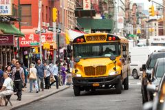 Yellow school bus driving through the streets of Chinatown in New York royalty free stock photo
