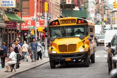 Yellow school bus driving through the streets of Chinatown in New York stock images