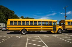 Yellow school bus parked in lot. Yellow school bus commonly used to transport children from home to learning institutions and back home Stock Images