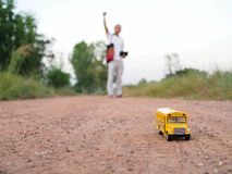 Yellow school bus plastic and metal toy model on the  country ro Stock Photos