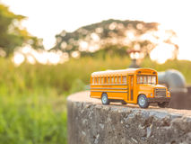 Yellow school bus plastic and metal toy model on the country roa. D stock images