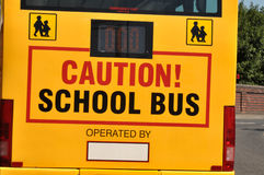 Yellow School Bus. Rear of a yellow school bus with caution sign and children crossing symbols Royalty Free Stock Photography