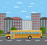 Yellow school bus on road in urban landscape Stock Images