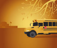 Yellow school bus in a school yard. Yellow school bus is standing in a school yard. Part of a school building is visible on a background. Branches of a tree are Royalty Free Stock Image
