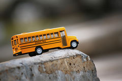 Yellow school bus toy model. Yellow school bus toy model on country road .Shallow depth of field composition Stock Image