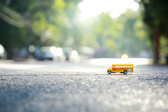 Yellow school bus toy model the road crossing. Royalty Free Stock Images
