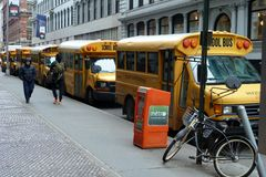 Yellow School Buses Line the Streets of New York. Yellow School Buses waiting to collect the children of New York. A propped up bicycle add to the image Stock Photos
