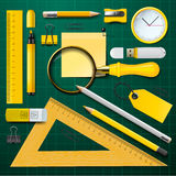 Yellow school supplies with green background Royalty Free Stock Image