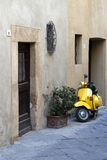 Yellow scooter. A yellow vespa scooter near a old house - Tuscany corner - Italy Stock Photos