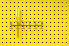 Yellow screwdriver sits in a rack on pegboard Stock Photos