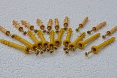 Yellow screws and dowels in a pile on a gray table stock photos