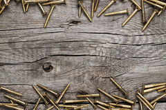 Yellow screws on the wooden table Royalty Free Stock Photos
