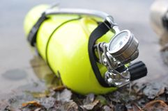 Yellow scuba tank. With attached pressure gauge and sidemount harness lying on a lake shore Stock Photos