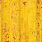 Yellow sea freight container background, rusty corrugated pattern, red primer coating, vertical rusted detailed steel texture. Crakcked grungy metal paint Royalty Free Stock Photo