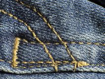 Yellow seam on jeans trousers stock image