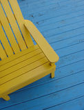 Yellow seat. Close up of a bright yellow adirondack chair on a bright blue wooden deck Stock Photos