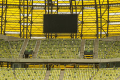 Yellow seats and electronic billboard display at stadium Royalty Free Stock Photography