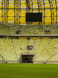 Yellow seats and electronic billboard display at stadium Stock Photos