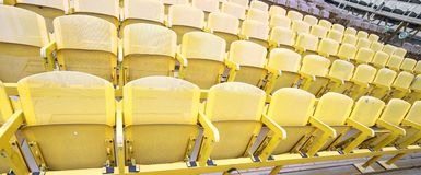 Yellow seats in the stands before the sporting event. Many yellow seats in the stands before the sporting event Royalty Free Stock Image