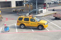 Security car in Airport. Yellow security car for Spring Airline is driving down a road in Airport Royalty Free Stock Photo