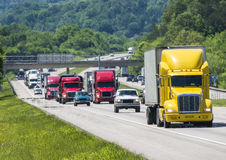 A yellow semi leads a packed line of traffic down an interstate in Tennessee. Heat rising from the pavement gives a shimmering effect to vehicles and forest Stock Photos