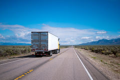 Yellow semi truck drive with commercial cargo by Nevada road Stock Photos