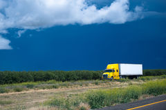 Yellow semi truck going thrue green bushes and trees Royalty Free Stock Images