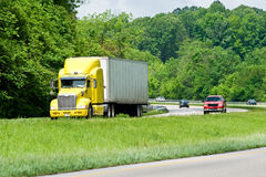 Yellow Semi Truck Leading Traffic On Highway Stock Photography