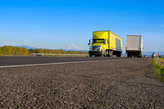 Yellow semi truck yellow trailer on road with asphalt rocks stock photography