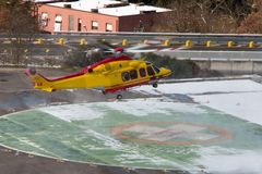 Medical helicopter landing. Yellow service medical elicopter landing in winter Royalty Free Stock Image