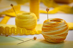 Yellow sewing thread and ribbons, landscape. Yellow sewing and embroidery thread with pins, ribbons, haberdashery Royalty Free Stock Photo