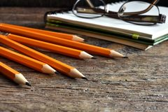 Yellow Sharpened Pencils and Notebook. A close up image of several wooden sharpened pencils and notebook on an old desk top Stock Image