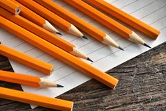 Yellow Sharpened Pencils and Paper. A close up image of several wooden sharpened pencils and paper on an old desk top Royalty Free Stock Photography