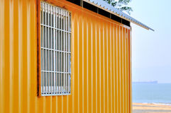 Yellow shed and sea view. Yellow shed at sea beach, with blue sea in perspective, shown as seaside view and color composition Royalty Free Stock Image