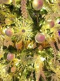 Yellow shimmering Christmas Decorations. Christmas tree decorations in yellow shimmering flowers and bows and royalty free stock image