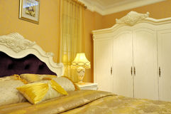 Yellow shining bedding and bedroom furniture. Yellow and shining bedding and pillow, with furniture and decoration in bed room, shown as comfortable and luxury Royalty Free Stock Photos