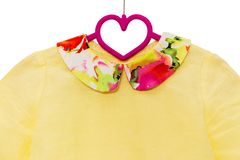 Yellow shirt on hanger with floral colar Royalty Free Stock Photos