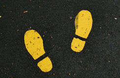 Yellow Shoe Prints. Yellow painted shoe prints on jogging track Stock Photos