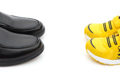 Yellow shoes for son and black ones for dad as filiation concept. Yellow shoes for son and black ones for dad on white as filiation concept Stock Images