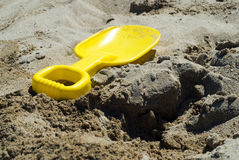 Yellow Shovel. A yellow shovel lying beside a shallow hole Royalty Free Stock Photos