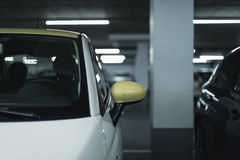 Yellow side mirror of car parked in garage. Royalty Free Stock Photos